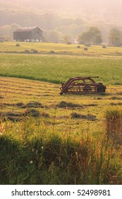 Farm Equipment With Farmhouse In The Distance