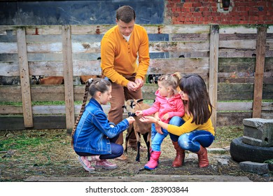 a farm family with a sheep in front of the farm