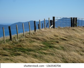 Farm fence on wind blown hilltop against rugged hill background