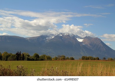 farm field with snow capped mountains, Smithers BC Canada