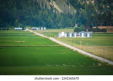 farm fields with silos near montana mountains