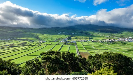 Farm fields in the Terceira island, Azores, high contrast with sun and back light over clouds