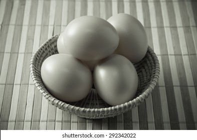 Farm fresh chicken eggs in a basket on rustic wooden background
