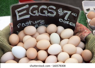 Farm fresh eggs for sale in a burlap covered basket at the farmers' market with a sign advertising price per dozen.