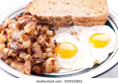 farm fresh eggs sunny side up with home fries and whole wheat toast