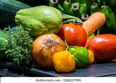 Farm fresh food ingredients clean and prepared for cooking. Colorful Jamaican vegetables & spices for dinner/ meal recipe. Kitchen countertop layout of onion, tomatoes, habanero/ scotch bonnet peppers