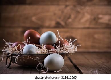 Farm fresh free range eggs in rustic bowl, on wooden table