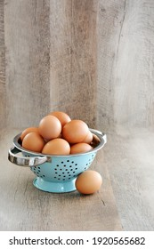 Farm fresh organic brown eggs in vintage aqua metal colander in vertical format with room for text.