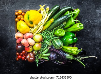 Farm fresh produce in a wooden box consisting of, peppers, beans, zucchini, squash, eggplant, tomatoes, peaches, pears and plumbs