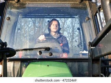 Farm hand behind the wheel of a tractor, seen through the windscreen