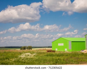 Farm hangars in pure sunny field. Agricultural background.