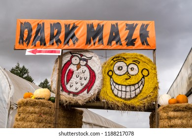 Farm Hay Bales Painted in Funny Faces and Sign for a Dark Maze for Halloween