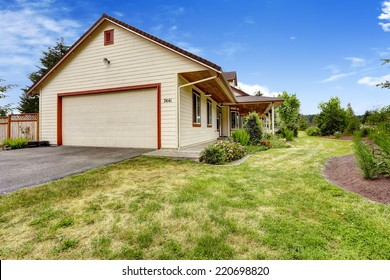 Farm house exterior with front yard landscape and garage with driveway
