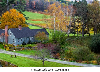 Farm house in green fields with colorful fall trees