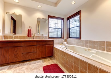 Farm house large bathroom with two windows, tile floor, cabinets and mirrors
