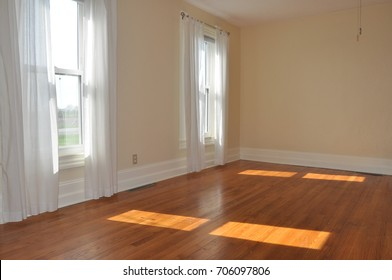 Farm House Room with Lace Curtains and Wood Flooring