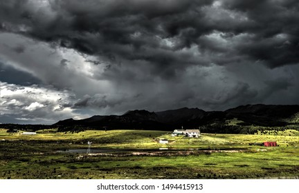 farm house under threatening cloudy sky southwest Colorado countryside in summer July