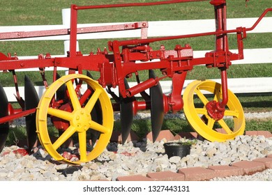 Farm machinery painted in bright yellow and red colors.