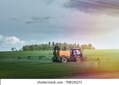 Farm machinery spraying insecticide to the green field, agricultural natural seasonal spring background.