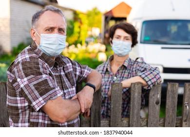 Farm neighbors in protective masks talk at the border of the garden plot