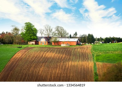 Farm on the top of a hill with cultivated fields under a blue sky