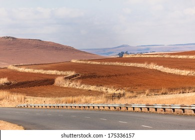 Farm Plowed Grooved Field Farm plowed earth field next to traveling road ready for seasonal planting in rural mountain countryside landscape
