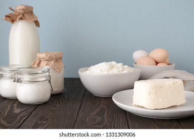 farm products: milk, yogurt, cottage cheese, butter, eggs on a wooden background