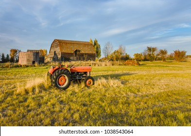 Farm in Saskatchewan, Canada A red tractor on the grass of a green field, near an old hut and a grain barn with a wooden hedge and a haystack. Trees and blue sky in the background.