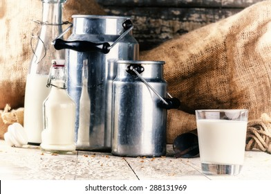 Farm setting with fresh milk in various bottles and cans