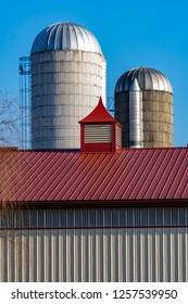 Farm silos stand near a red barn roof.