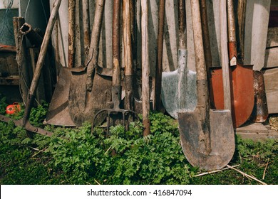 Farm tools in front of a wooden old barn