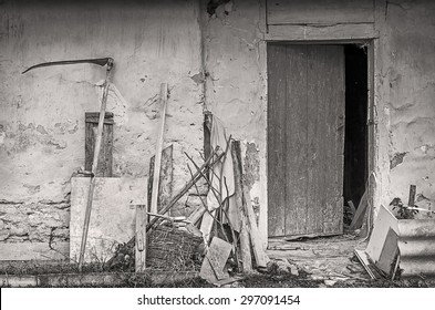 Farm tools near wall of old shed. Black and white photo.