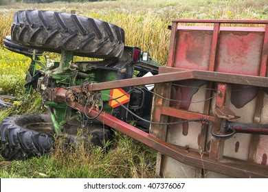 A farm tractor and the attached cart lay on their side in a ditch in rural Ontario Canada.