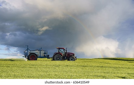 farm tractor carrying spraying chemicals on a spring field