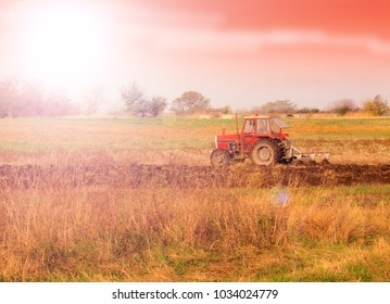 Farm Tractor in a field on a  Farm at sunset