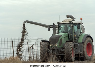 A farm tractor fills its liquid manure from the tank trailer into a manure depot. Manure is used as fertilizer in agriculture. Concept: agriculture