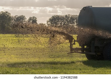 A farm tractor sprays its manure from the tanker onto a field. Manure is used as fertilizer in agriculture. Concept: agriculture