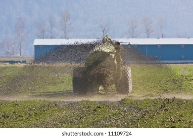 Farm tractor spreading manure before spring seeding