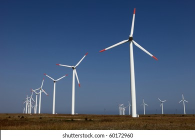 Farm of wind turbines against a blue sky