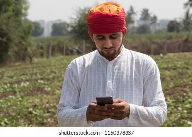 Farm worker text messaging on mobile phone in rural field