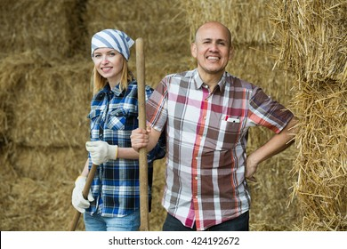 Farm workers with pitchforks posing in hayloft and smiling