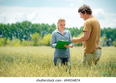 Farmer and agronomist discussing about future crop of wheat, at the field