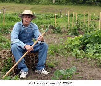 farmer in bibs and straw hat sitting on a straw bale