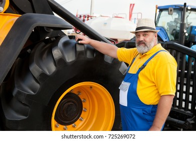 farmer in blue overalls from agricultural machinery
