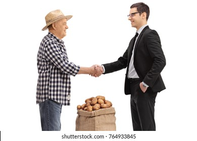 Farmer with a burlap sack filled with potatoes shaking hands with a businessman isolated on white background