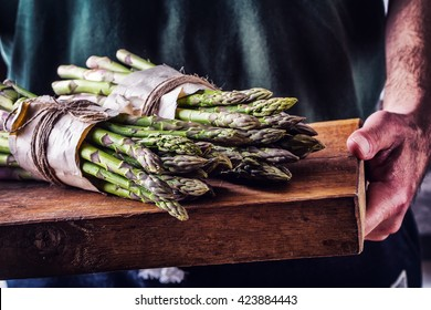 Farmer carries tied asparagus on a wooden board.