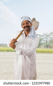 Farmer carrying hoe on his shoulder standing in field