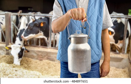 farmer with a churn of milk in front of a herd of cows