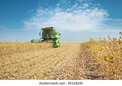 A farmer combines a field of soybeans