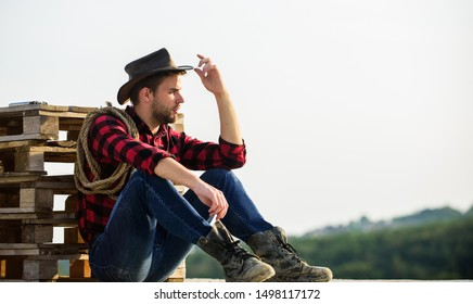 Farmer enjoy view from his farm. Peaceful mood. Watching sunset. Farmer cowboy handsome man relaxing after hard working day at ranch. Romanticism of western culture. Farmer in hat sit relax.